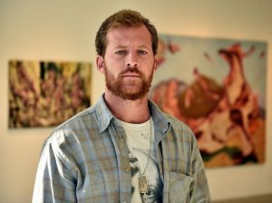 """Artist Jacob Cullers stands in the gallery at Three Rivers Community College where his work is on display in a show titled """"Castles Made of Sand."""" Cullers' brother, U.S. Army Staff Sgt. Ari Cullers, was killed by enemy fire in Afghanistan in October of 2011. (Sean D. Elliot/The Day)"""