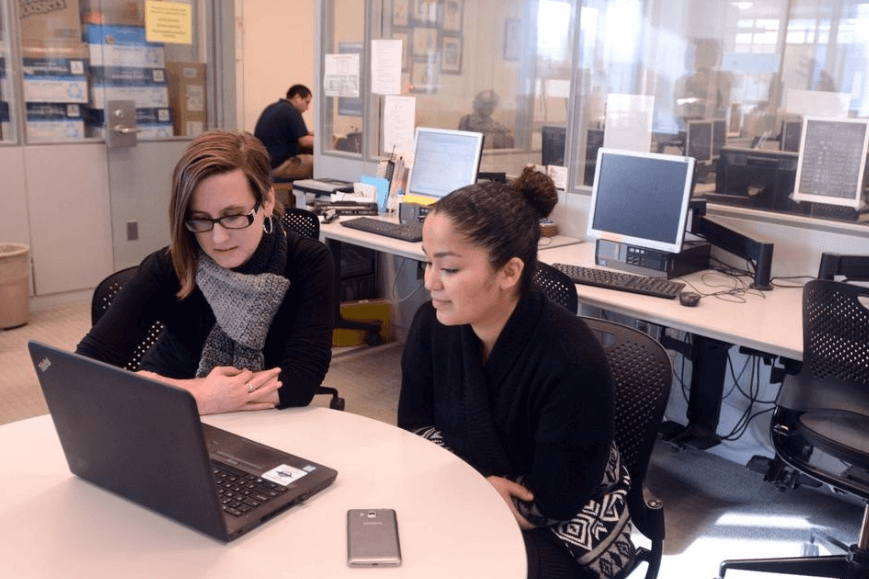 Education Assistant Kathryn Warrender, left, works with Aliana Williams-Gaines of Norwich in the Writing Lab at Three Rivers Community College Tutoring Center.