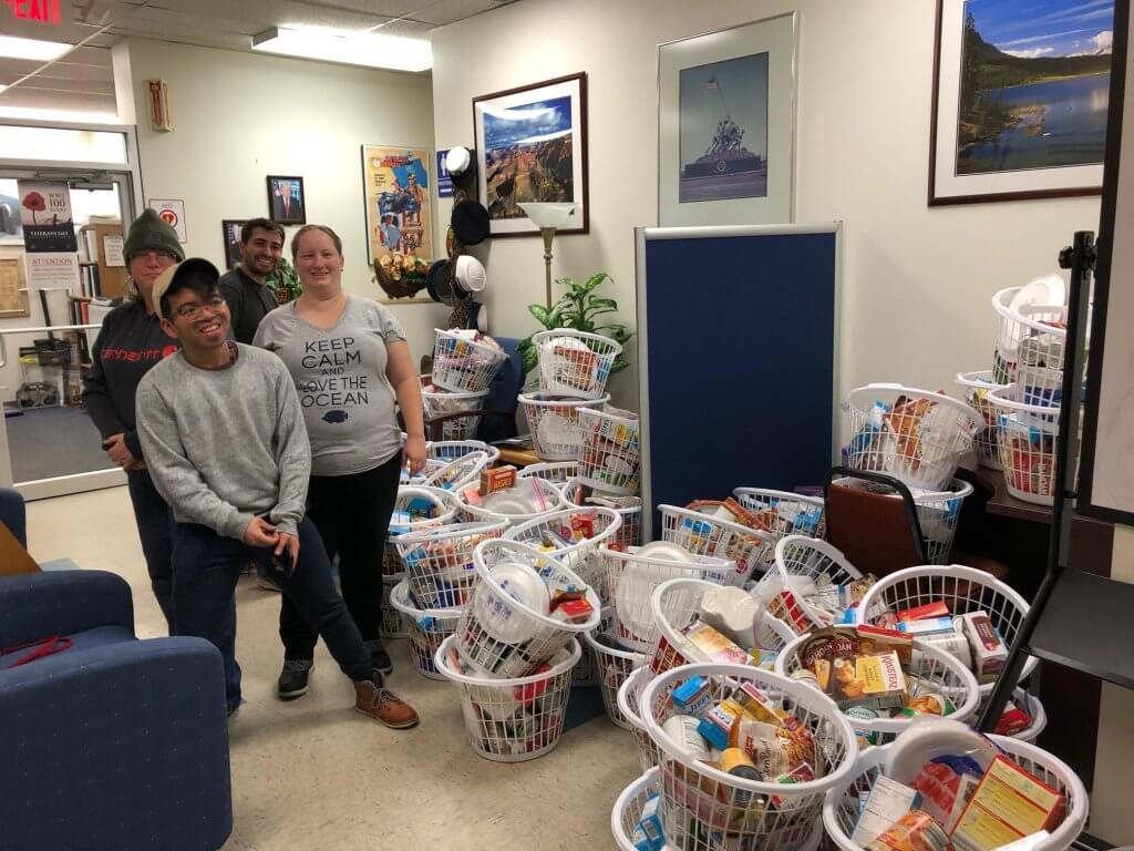 (Left to right) Three Rivers Community College students Thena Cranfill, Joe Victorino, Cody Sowell, and Marie Parry pose with some of the 80 Thanksgiving dinners they delivered to the Norwich Vet Center.