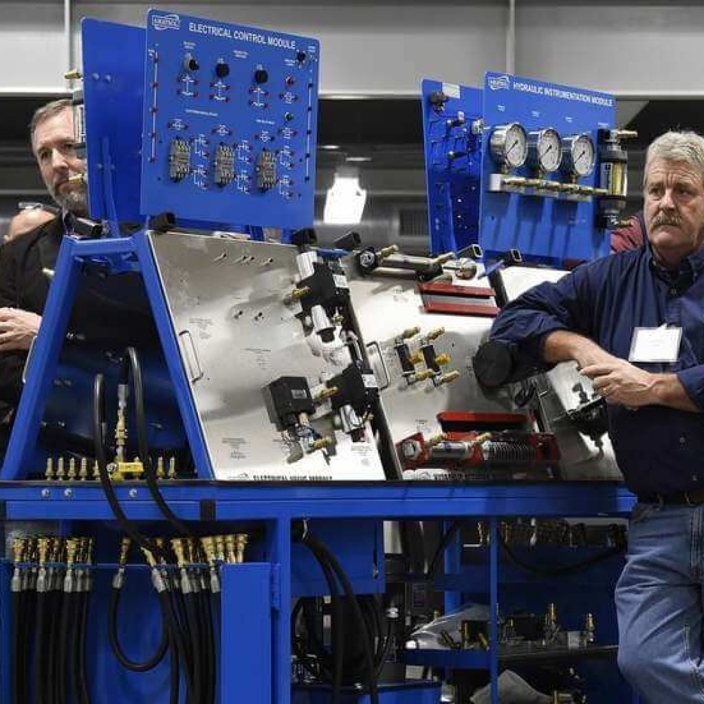 People stand among some of the trainers for electronics, hydraulics, pnuematics, and mechanics while listening to one of the speakers during the ribbon cutting ceremony at the new Three Rivers Community College Manufacturing Apprenticeship Center at Grasso Tech in Groton on Tuesday, Nov. 19, 2019. (Dana Jenson/The Day)