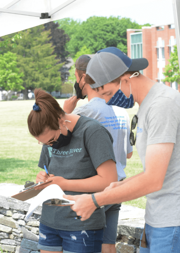 students handing out degrees