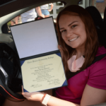 student smiling with degree
